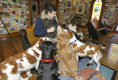 Vermont folk artist Stephen Huneck, sits in his dog chapel in St. Johnsbury, Vt. Huneck, who started out whittling wooden sculptures of dogs and now specializes in dog-themed furniture, woodcut paintings and children's books, has carved out a unique niche with his whimsical reproductions of dogs.