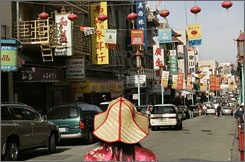 A woman looks at Chinese New Year banners hanging along a street in the Chinatown neighborhood of San Francisco.