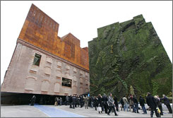 People queue to enter the new Caixa Forum arts center in Madrid, Spain. The Caixa Forum is an old electricity station and a new cast iron extension has been added to the original structure.