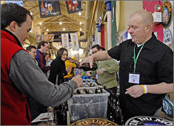 Bob Erdman, right, pours Unibroue beer for a visitor at the Philly Craft Beer Festival in Philadelphia.