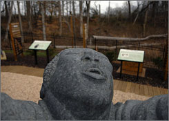 """Hallelujiah,"" center, a stone sculpture of a slave, his freed arms outstretched to the sky, sits in the ""Spirit of Freedom Exhibit Garden"" where the proposed United States National Slavery Museum in Fredericksburg, Va. is planned."