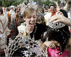 Dana Kurth, left, reacts as she and other members of the the Fiesta court break cascarones, or confetti eggs, over each other during the 2007 Fiesta in San Antonio.