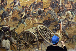"A conservator works on a section of the 377-foot ""Battle of Gettysburg"" cyclorama painting."