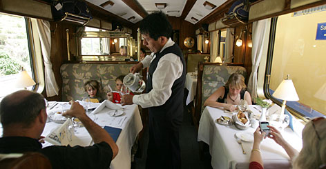 Tourists eat on the PeruRail train that links Cuzco and the famous ruins of Machu Picchu. Despite an expanding economy, poverty still affects 44% of Peru's population, and some residents fear they won't profit from the tourism boom.