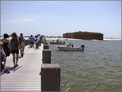 Visitors walk towards Fort Massachusetts after arriving at West Ship Island at the Gulf Islands National Seashore, Miss.