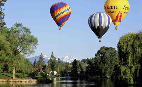 Up, up and away: Hot-air balloons float over the Deschutes River with the Cascade Mountains in the background near downtown during Balloons Over Bend, one of the city's annual festivals.