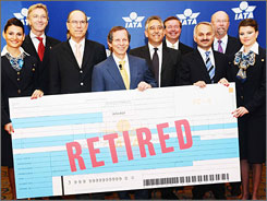 Officials of the International Air Transport Association pose with a replica of the final paper airline ticket.  The IATA will stop issuing paper ticket stock to travel agencies and airlines around the world.