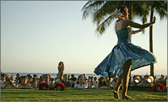 A dancer performs during a torch-lighting and hula show on Kuhio Beach in Waikiki. Hawaii is expecting a 3% overall drop in visitor numbers this year compared to 2007.