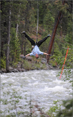 "Head over heels for ziplining: Simon Richardson, a ""sky ranger"" with Soaring Tree Top Adventures, zooms across the raging Animas River in Colorado. Ziplining was popularized in the rain forests of Costa Rica."