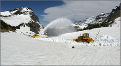 Plows work to clear Glacier National Park's Going-to-the-Sun Road in 2006. The road's 75th anniversary celebration will be held this year.