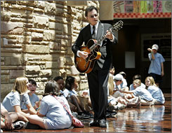 Guitarist David Andersen performs for a group of students from Russelville, Ala., as they wait to tour the Country Music Hall of Fame and Museum in Nashville.