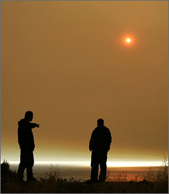 IN BIG SUR: Firefighters from the Hoopa Indian Reservation observe the sun obscured by smoke over the Pacific Ocean.