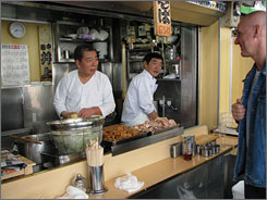 AT THE INOE FOOD STALL: Katsu Matsuoka, left, and Hajime Kawahara prepare a bowl of ramen noodle soup for Freddy Schmidt, executive chef of the Conrad Tokyo hotel.