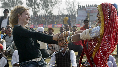 A tourist performs with a folk dancer in Rajasthan, a region in western India famous for its fabulous splash of colors, medieval forts, ancient temples and camel safaris.