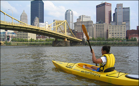 A kayaker paddles through downtown Pittsburgh, which was built on the confluence of the Monongahela and the Allegheny rivers.