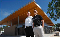 Designers Ryan Brouwer and Randy Pease pose in front of the new environmentally friendly toilet-shower building in Michigan's Grand Haven State Park. The restroom is the first of its kind in the state park system.