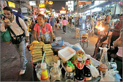 A food vendor moves through heavy tourist traffic on Khao San Road.