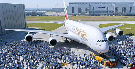Airbus employees line the tarmac in Hamburg as Gulf airline Emirates takes delivery of its first Airbus A380 superjumbo. The carrier plans to add 57 more A380s to its fleet in the coming years.