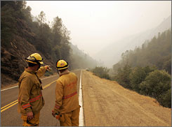 Firefighters look over Highway 140, near the west entrance to Yosemite National Park, as flames from the Telegraph Fire rise from along the bed of the Merced River. Smoke from the fire is obscuring the views at many of Yosemite's signature attractions.