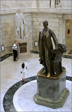 Tourists pose for pictures with the Jefferson Davis statue as Abraham Lincoln towers in the foreground at the Capitol Rotunda in Frankfort, Ky.