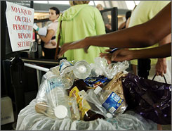 Passengers dispose of plastic bottles before a security checkpoint at Washington Dulles airport.
