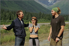 Host Phil Keoghan, left, greets winners Rachel Rosales and TK Erwin at the finish line in Alaska during the 12th season of The Amazing Race.