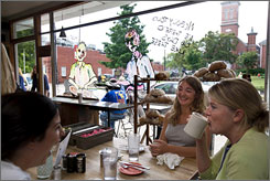 Everyone's a friend: Mary Catherine Williams, left, Erica Newman and Lauren Babbitt have coffee at Oxford's Bottletree Bakery under a likeness of John McCain and Barack Obama taking coffee together, too.