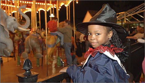 A young visitor waits for her turn on the carousel during the Audubon Zoo's annual Halloween celebration in New Orleans.