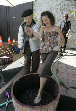 Winemaker Mike Grgich helps Beverly Miller of Akron, Ohio, into a barrel of Zinfandel grapes to do some stomping.