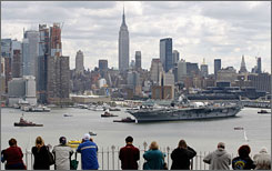 People in Weehawken, N.J., watch as the decommissioned aircraft carrier Intrepid is towed back to its home port on the Hudson River in New York.