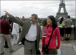 Christian Ragil of France, left, guides Ju Young Gam of South Korea, as they tour the Trocadero plaza near the Eiffel tower, seen behind.