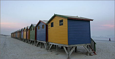 Changing huts line the beach in Muizenberg, Cape Town's surfing hotspot. The city's magnificent scenery and excellent infrastructure make it a favorite among wealthy surf and safari seekers.