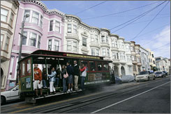Visitors ride the Powell-Mason cable car along Mason Street in San Francisco. The city has three cable lines, each with its own flavor.