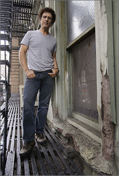 Tin Pan Alley tenant Leland Bobbe stands next to a crumbling window frame outside his apartment. Bobbe, other tenants and preservationists are unhappy that the group of buildings, once home to songwriters like George and Ira Gershwin and Irving Berlin, could be replaced by high-rises.