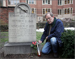 """Jeff Jerome, curator of the Poe House and Museum in Baltimore, poses next to items left at Edgar Allan Poe's grave by the mysterious """"Poe Toaster."""""""