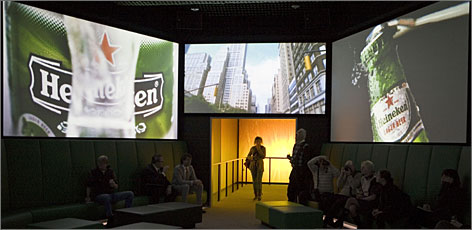 Visitors watch commercials at the Heineken Experience in Amsterdam. The museum reopened in December after a major renovation.