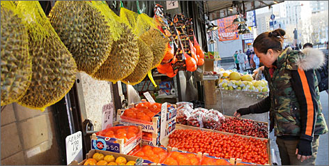 Many Chinatown markets have open-air displays of fish, vegetables and fruit like the exotic green durian (seen here in bags).
