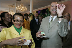Mayor Ray Nagin, joined by his wife Seletha,  pulls a plastic baby from his slice of king cake at Gallier Hall in New Orleans.