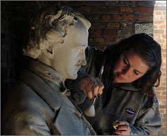 His memory stands: Laura Curzi cleans a bust of the author at Richmond's Poe Museum, the oldest of four museums dedicated to him.
