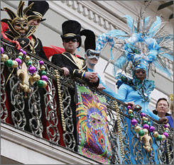 Mardi Gras revelers  watch the Bourbon Street Awards Show from a balcony  in the French Quarter of New Orleans.