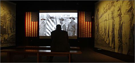 In Philadelphia: Tavis Smiley watches a video on blacks in the military at his exhibit, America I AM.