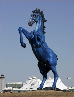 "The 32-Foot blue ""Mustang"" sculpture is seen at Denver International Airport with the terminal in the background. A year after it was installed, Luis Jimenez's sculpture has become a hot topic of conversation."