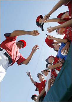 Los Angeles Angels third base coach Dino Ebel signs autographs before a spring training game in Tempe, Ariz.