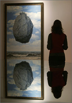 A visitor looks at Magritte's The Castle of the Pyrenees at the Cincinnati Art Museum.