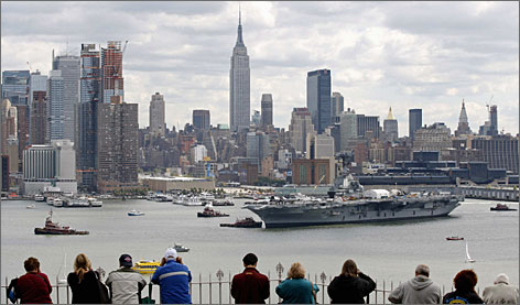 Weehawken, N.J.: Visitors gather to watch as the World War II carrier Intrepid is towed to its home port on the Hudson River.