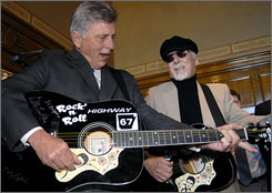 Arkansas Gov. Mike Beebe, left, and rockabilly musician Sonny Burgess perform during the bill signing at the Capitol in Little Rock, Ark.