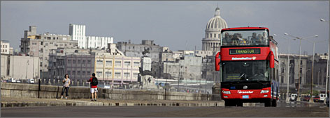 A tour bus passes sightseers on Havana's Malecon. Officials say they have taken no special precautions to prepare for more Americans.