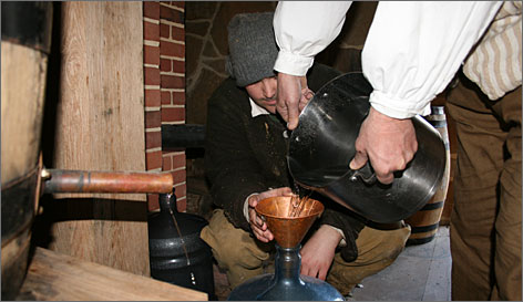 Mount Vernon workers empty a finished pot of whiskey into a jug for storage. The whiskey is clear until it is aged.