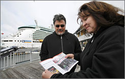 Philip, left, and Yolanda Tabet, of Belen, N.M., examine a brochure of downtown Seattle as they walk past their cruise ship, the Royal Caribbean Mariner of the Seas. Swine flu fears have led cruise lines to alter itineraries that were previously scheduled to stop in Mexico.