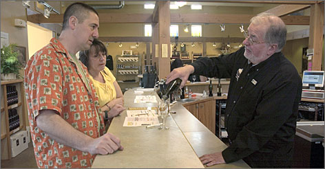 George Siefert, manager of The Round Barn Winery store in Union Pier, Mich., pours a sample for customers.